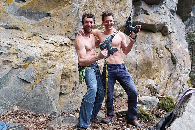Das Bild zeigt zwei Kletterer ohne T-Shirt. Sie stehen mit gehobenen Bohrmaschinen in je einer Hand ohne T-Shirt da und umarmen sich in der Mitte freundschaftlich. Im Hintergrund oranger Fels.