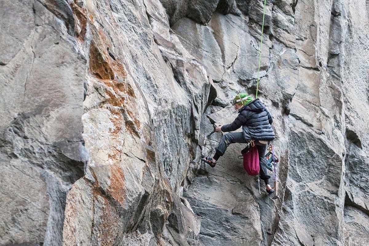 DAs Bild zeigt einen Kletterer beim Ausbouldern der züge in einer neuen Route. An einer grau-braunen Felswand hängt der Kletterer im rechten Bildteil im Seil und versucht einen Kletterzug. Er trägt eine schwarze JAcke und Mütze weil es windig und kalt ist.