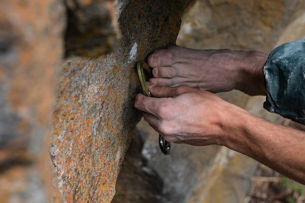 Das Bild zeigt die Markierung der Haken Position beim Kletterroute einbohren. Eine Hand hält eine Express Schlinge zum markierten Punkt am Felsen.