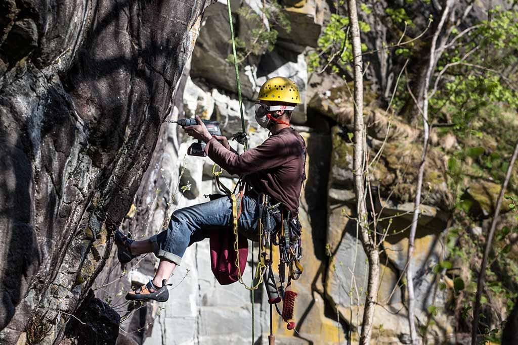 DAs Bild zeigt einen Kletterer beim Einbohren. Er hängt im Seil und bohrt mit einem Akku Bohrhammer im Fels. Er trägt lobenswerter Weise alle Teile der Schutztausrüstung wie Helm, Schutzbrille und Atemmaske.
