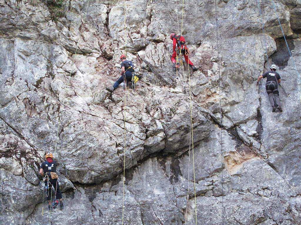 Das Bild zeigt eine graue Felswand mit vier Männern während einer Klettergarten Sanierung. Sie hängen mitten in der Wand und erledigen die Einbohr Arbeiten.