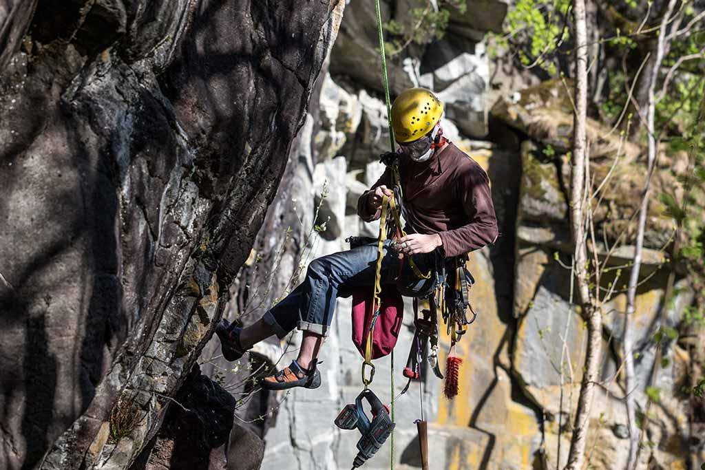 Das Bild zeigt einen Kletterer beim Einbohren.Er hängt im Seil und sortiert gerade seine Ausrüstung am Gurt. Links schwarzer Feld, in Bildmitte der Kletterer, im Hintergrund heller, oranger Felsen.