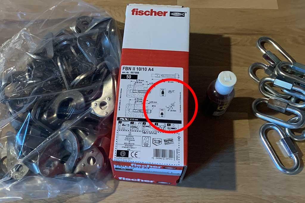 Das Bild zeigt wo der Drehmoment bei Bohrhaken auf der Produktverpackung zu finden ist. Auf dem Bild ist links ein Sack mit Bohrhakenlaschen zu sehen. In der Mitte eine Karton mit Bohrhaken. Rechts mehrere Rapid Glieder. Am Karton ist mit einem roten Kreis die Stelle markiert, wo der richtige Drehmoment bei Bolzenankern angegeben ist.
