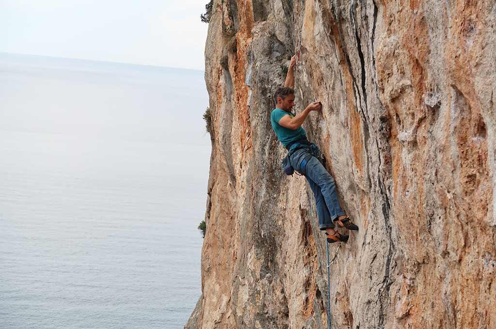 Das Bild zeigt einen Klettergarten in Meeresnähe. Er befindet sich in der Kletterdestination Leonidio in Griechenland. Ein Kletterer befindet sich in einer grau-orangen Felswand, im Hintergrund sieht man das Meer.