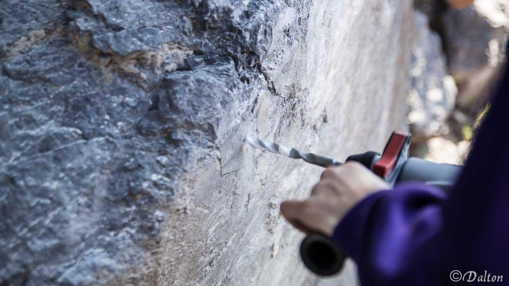 Das Bild zeigt einen Vorgang beim Setzen eines Bohrhakens. Im rechten Bildteil sieht man eine Hand und einen Akku Bohrhammer mit einem Bohrer der auf einen weißen Felsblock im linken Bildteil gedrückt wird.