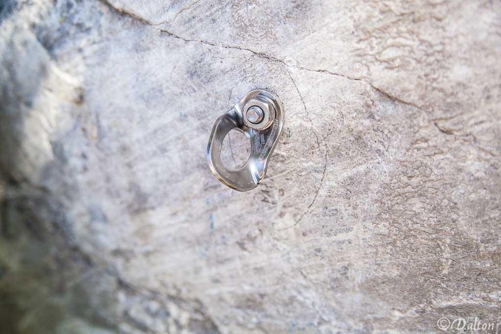 Das Bild zeigt eine verbogene Bohrhakenlasche nach einem Auszugstest. Sie befindet sich auf weißem Fels in Bildmitte, ist silber glänzend und sichtlich verbogen.
