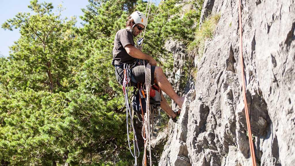 Das Bild zeigt einen Kletterer während einer der Einbohr Kurse von bolting.eu. Er seilt sich ab und sortiert gerade sein Seil.
