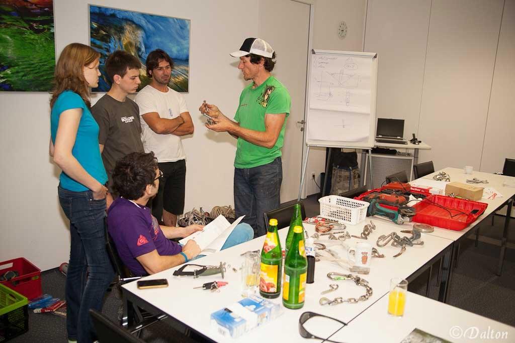 Das Bild zeigt einen Theorievortrag der bolting.eu Academy. In einem Seminarraum stehen mehrere Teilnehmer mit dem Vortragenden zusammen und diskutieren über Bohrhaken. Im Vordergrund rechts die Tische mit Vortragsunterlagen und Einbohr Materialien.