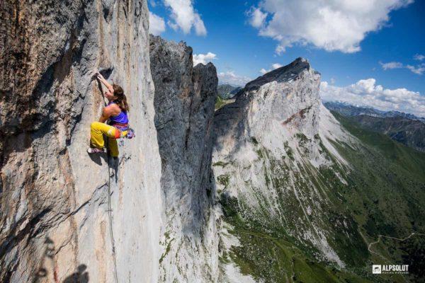 Das Bild zeigt die Frictionlabs Athletin Babsi Zangerl. Sie klettert im Sonnenschei an einer grauen Felswand im Gebirge. Hinter ihr zieht sich eine Bergkette mit abfallender Felswand bis in den Hintergrund. Der Himmel ist blau mit ein paar Wolken.