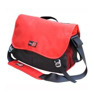 Das Bild zeigt die Bouldertasche Bee Bag von i´bbz. Sie steht leicht schräg im Bild sodass man die gesamte Vorderseite des roten Messenger Bags erkennen kann. Im Vordergrund der Trageriemen.