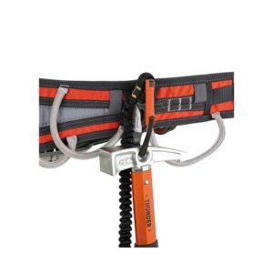 Das Bild zeigt den schwarz-orangen Climbing Technology Materialkarabiner Hammer Lodge auf einem schwarz-orangen Klettergurt montiert. Darin ist ein Felshammer am Hammerkopf eingehängt.