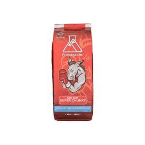 Das Bild zeigt eine rote Packung Frictionlabs Bam Bam Chalk. Man sieht die aufrecht stehende Packung von der Vorderseite mit dem Logo, dem Pferd Logo und dem Produktnamen darunter.