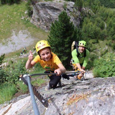 Das Bild zeigt ein Kind mit Vater am Klettersteig. Der Junge hat einen Kletterhelm Kinder Fixe auf und lächelt in die Kamera.