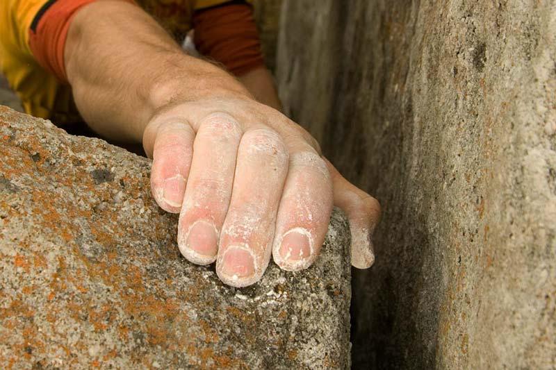 Das Bild zeigt eine angechalkte HAnd eines Kletterers auf einem Felsblock.