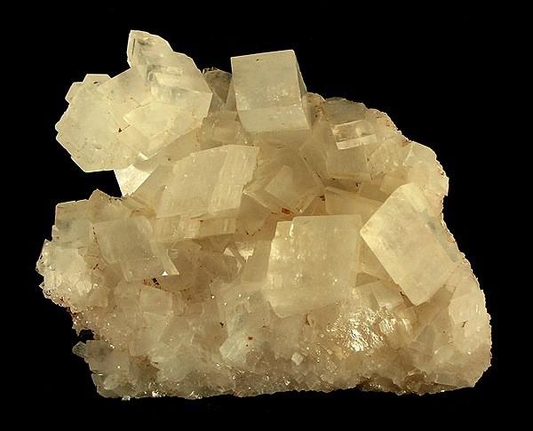 Das Bild zeigt einen Magnesit Kristall mit würfeligen Strukturen an der Oberfläche