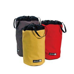Das Bild zeigt drei bunte Metolius Big Wall Stuff Sacks Materialsäcke. Im Vordergrund einen gelben,links hinten einen grauen und rechts hinten einen roten.