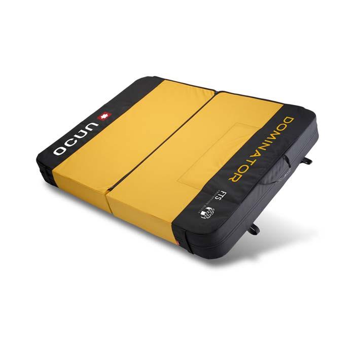 Das Bild zeigt einen großen Bouldermatten Typ, ein sogenanntes Fat Pad. Es steht schräg in Bildmitte und hat ein gelbes Center sowie schwarze Außenränder.