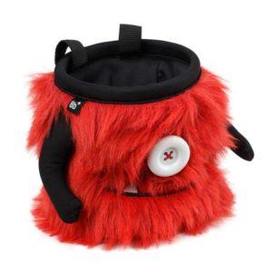 Das Bild zeigt das Chalkbag Monster Bruno von schräg links oberhalb. Der rote, lustige Magnesiumbeutel haut einen Knopf als Auge und einen Mund mit zwei spitzen Zähnen sowie zwei seitlichen Armen.