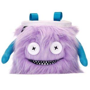 Das Bild zeigt das Chalkbag Monster Lilly von leicht links oberhalb. Der violette, lustige Magnesiumbeutel hat zwei Knöpfe als Augen und einen Mund mit vielen kleinen Zähnen sowie zwei seitliche Arme.