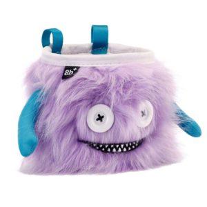 Das Bild zeigt das Chalkbag Monster Lilly von vorne. Der violette, lustige Magnesiumbeutel hat zwei Knöpfe als Augen und einen Mund mit vielen kleinen Zähnen sowie zwei seitliche Arme.