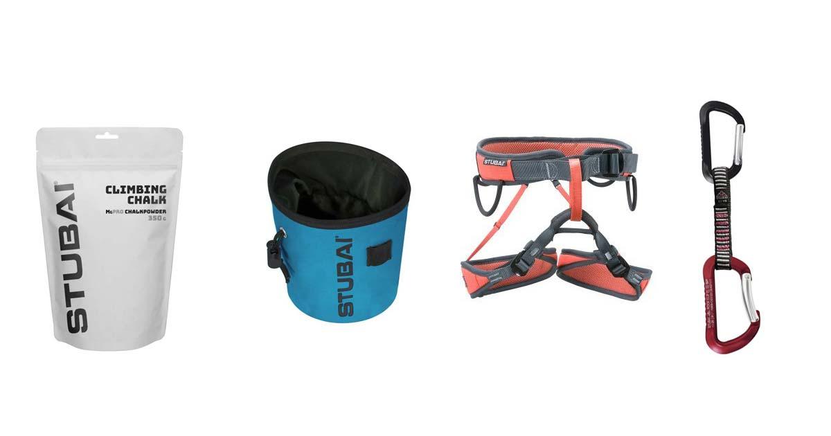 Das Bild zeigt vier Kletterausrüstung Artikel von Stubai Bergsport. In einem weißem,länglichen Rechteck sind zu sehen von links nach rechts: eine Packung Chalk, ein blaues Chalkbag, ein schwarz-roter Klettergurt und eine Expressschlinge.