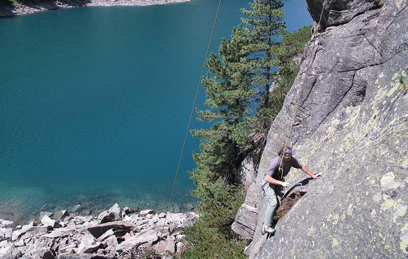 Das Bild zeigt einen Kletterer beim Putzen einer Route. Er ist in einer grauen Felswand, im Hintergrund links ein See und ein paar Bäume.