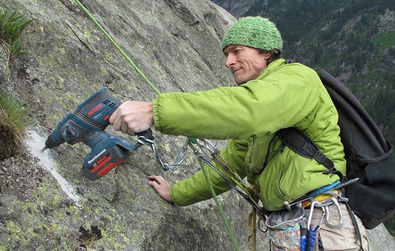 Das Bild zeigt einen Kletterer beim Setzen eines Bohrhakens. Er hängt in einer Felsplatte und bohrt im Bildvordergrund mit einem Akku Bohrhammer in den Fels.