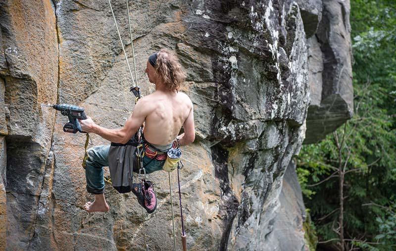 Das Bild zeigt einen Kletterer beim Setzen eines Bohrhakens. Er befindet sich in Abseilhaltung in der Wand und bohrt mit der linken HAnd im Fels. Rechts im Hintergrund grüne Bäume.