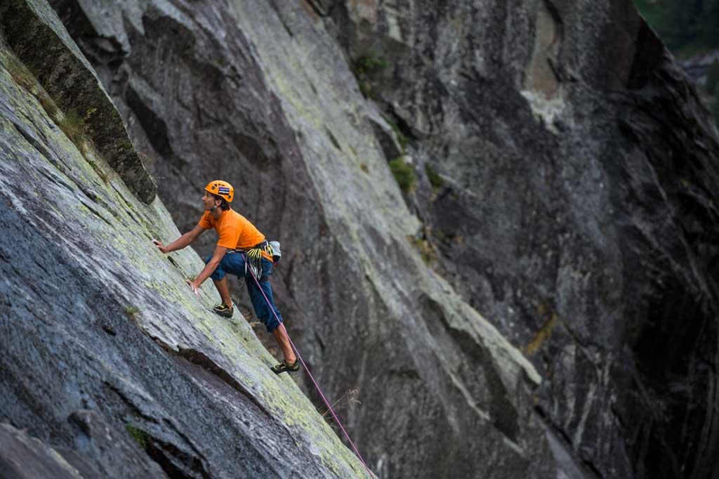 """Das Bild zeigt passend zum Thema """"Kletterroute mit Bolts erschließen"""" eine Kletterer auf einer Granitplatte. Er trägt einen orangen Helm und T-Shirt und sticht auffällig vor dem dunklen Fels hervor. Das Bild veranschaulicht die wohl beste Felsart, Granit, für die Anwendung von Bohrhaken."""