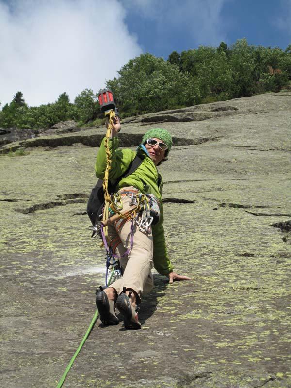 Das Bild zeigt einen Kletterer in einer Felswand. Er will gerade eine Kletterroute mit Bohrhaken einrichten und steigt deshalb im Vorstieg eine Platte empor. Er blickt gerade zurück und hebt zum Spass die Bohrmaschine wie zum Gruß.