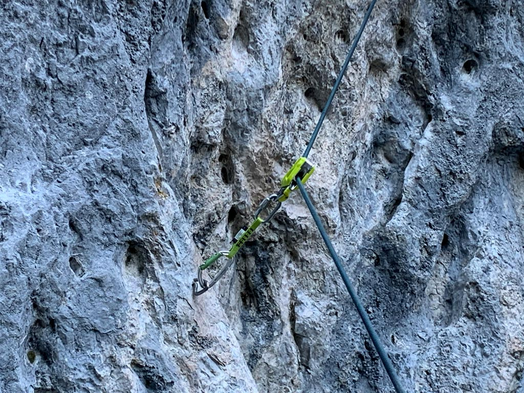 Das Bild zeigt ein nach oben gezogenes Edelrid Ohm nach dem Ablassen. Vor einer grauen Felswand hängt der Vorschaltwiderstand am Seil schräg nach oben.