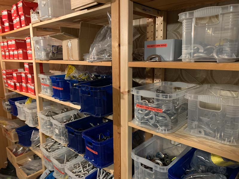 Das Bild zeigt Einbohrartikel im Lager des SPezialisten bolting.eu. In mehreren Regalen befinden sich unzählige Lagerboxen mit Klebehaken, Bohrhakenlaschen, Bohrhaken und Kettenständen.