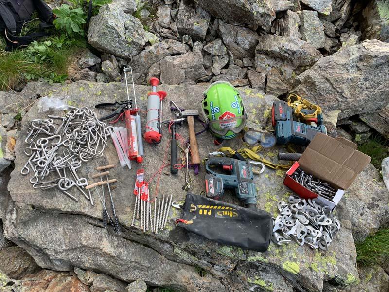 Das Bild zeigt sortierte Einbohrartikel bei einer Klettergarten Sanierung. Zu sehen ist Kletterausrüstung sowie verschiedene Hardware wie Bohrhakenlaschen, Bohrhaken, Klebehaken, Injektionsmörtel und Kettenstände.
