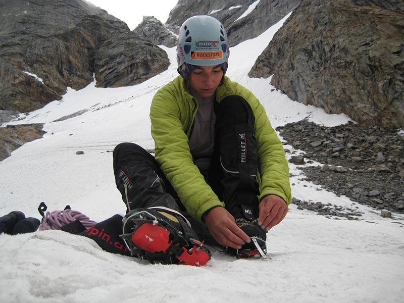 Das Bild zeigt eine Bergsteigerin beim Anlegen ihrer Steigeisen. Es soll die Wichtigkeit dieses Produktes in der Hochtouren Ausrüstung darstellen.