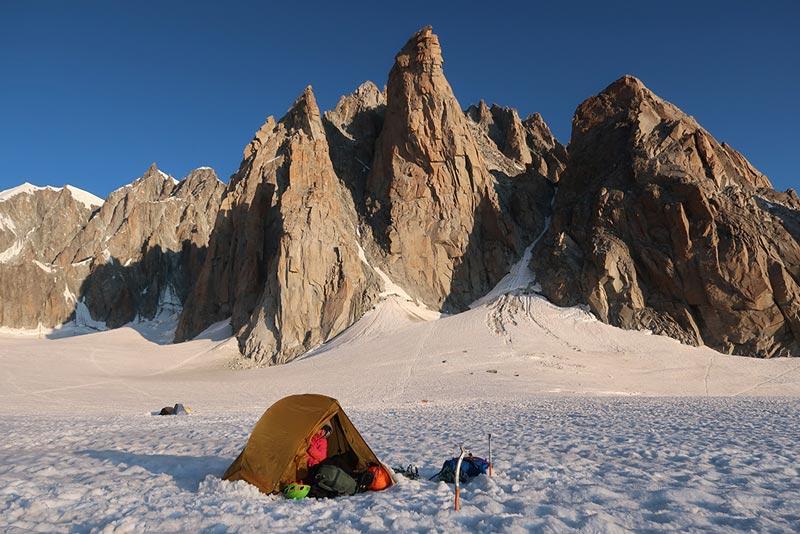 Das Bild zeigt ein Zelt mit Teile der Hochtouren Ausrüstung davor am Gletscher. Im Hintergrund die große Westwand des Grand Cappucin im Montblanc Gebiet.
