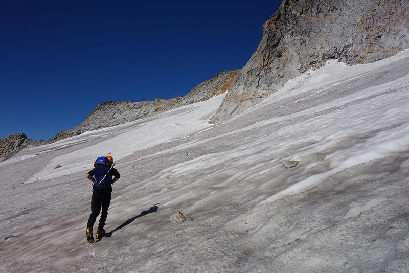Das Bild zeigt einen Bergsteiger mit passender Hochtouren Ausrüstung auf einem Gletscher. Er geht schräg durch das Bild, im Hintergrund ein Felsgrat und tiefblauer Himmel.