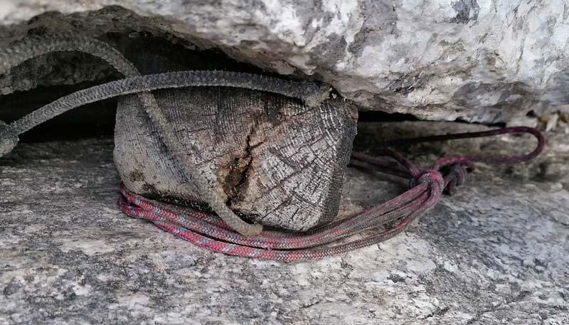 Das Bild zeigt einen Vorgänger des heutigen modernen Klemmkeil, nämlich einen alten Holzkeil mit Reepschnüren umwickelt. Er steckt in einem Kalk Riss und zeigt deutliche Spuren seines hohen Alters.