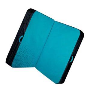 Das Bild zeigt das Beal Double Air Bag Crashpad. Die Bouldermatte liegt leicht schräg und in geöffnetem Zustand in Bildmitte. Man erkennt die hellblaue Innenseite, die schwarze Außenseite und die Trageriemen.