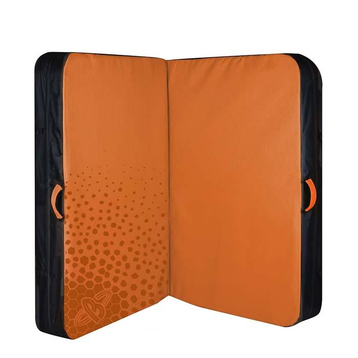 Das Bild zeigt die Beal Jumbo Pad Bouldermatte. Die orange Matte steht aufgeklappt und stehend in Bildmitte. Man erkennt die gepunktete Oberseite, die schwarze Unterseite sowie die seitlichen trageriemen.