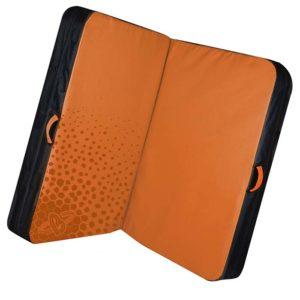Das Bild zeigt die Beal Jumbo Pad Bouldermatte. Die orange Matte liegt aufgeklappt und leicht schräg in Bildmitte. Man erkennt die gepunktete Oberseite, die schwarze Unterseite sowie die seitlichen trageriemen.
