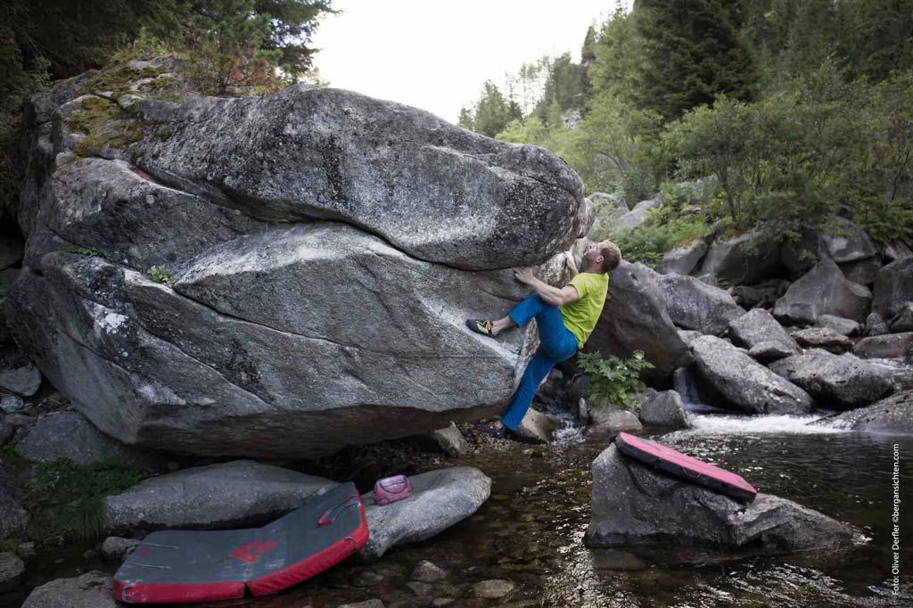 Das Bild zeigt eine Szene beim Bouldern neben einem Bach. Es soll die Wichtigkeit der Boulderausrüstung zeigen, denn es liegen zwei Bouldermatten auf spitzen Steinen unter dem Kletterer.