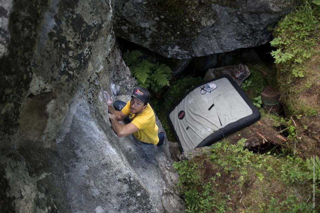 Das Bild zeigt ein Beispiel für den Boulderausrüstung Gegenstand Bouldermatte. Unter einem Boulderer mit Schildkappe und gelbem Shirt befindet sich ein Moon Crashpad.