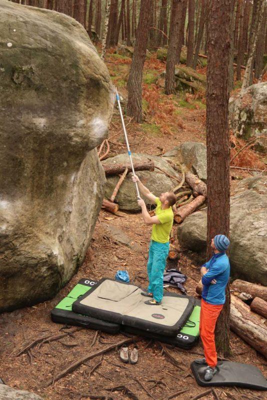 Das Bild zeigt ein Beispiel für den Boulderausrüstung Gegenstand Teleskop Putzstock. Ein Boulderer steht am Boden und putzt mit der Boulderbürste am Ende de Stocks einen Griff in ca. drei Metern Höhe.