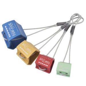 Das Bild zeigt ein Set der DMM Wire Torque Nuts. Die vier bunten Klemmkeile liegen schräg in Bildmitte. Die Alu Köpfe mit den Drahtschlingen sind perfekt zu erkennen.