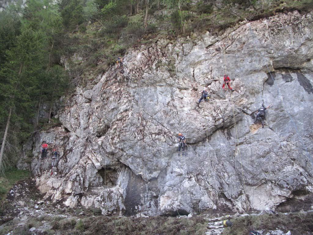 Das Bild zeigt wie Einboihr Kurse bei bolting.eu ablaufen können. Es hängen sechs Kletterer arbeitend in ineiner grauen Felswand. Man erkennt dass sie alle am Arbeiten sind und der Fels hergerichtet wird.