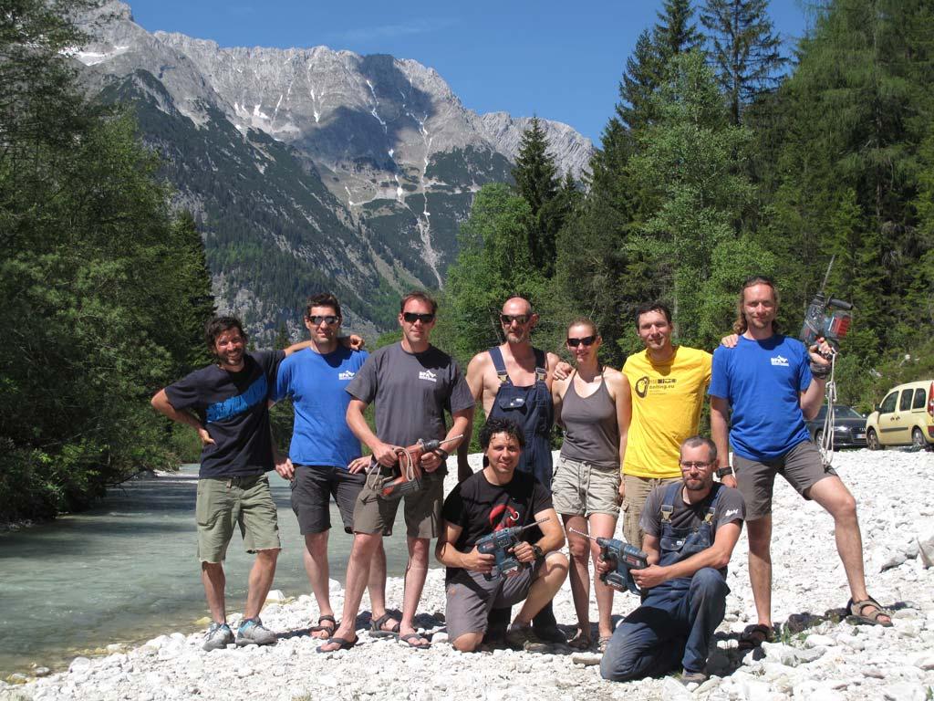 Das Bild zeigt eine Gruppe an Kletterern bei einem Kurs von bolting.eu. Sie stehen im Sonnenschein in einer Gruppe an einem Flus szusammen. Einige Personen halten eine Bohrmaschine in der Hand.