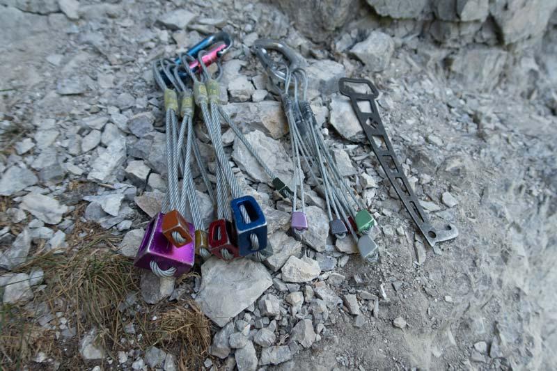 Das Bild zeigt ein durchschnittliches Alpinkletter Klemmkeil Set. Auf Kalkfels liegt ein Standard Klemmkeil Set, ein Set Offset Nuts und ein Klemmkeilentferner.