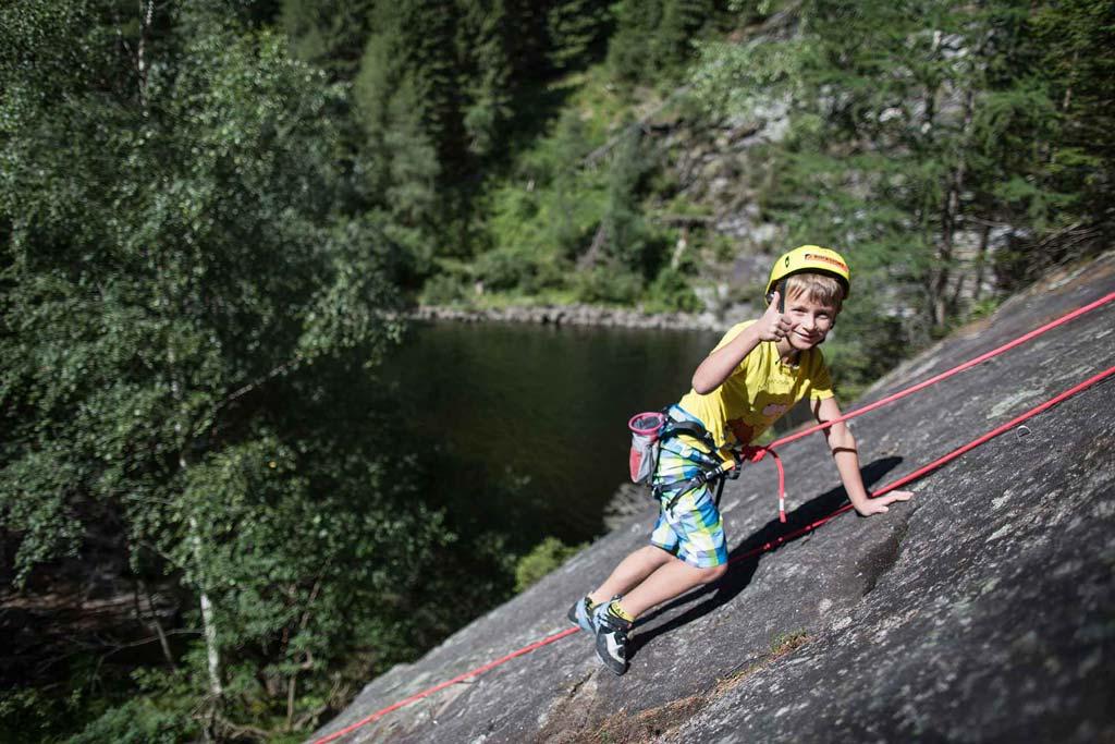 Das Bild zeigt eines der Massive des Maltatal Kletterführer. Ein Junge mit gelben HElm klettert an einer grauen FElsplatte. Im Hintergrund ein Fluss. Der kleine Bube zeigt ein Thumbs up in die KAmera.