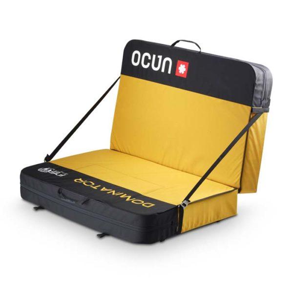 Das Bild zeigt die Ocun Dominator Bouldermatte. Das Pad liegt im Couch Modus in Bildmitte. Man erkennt die gelb-schwarzen Hälften und die seitlichen kleinen Schnallen Ösen wo die Bänder die Hälften fixieren.