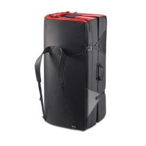Das Bild zeigt die Ocun Incubator Bouldermatte. Das Crashpad steht zusammengefaltet und aufrecht in Bildmitte. Man erkennt die schwarze Außenhülle, die Trageriemen und die rote Innenseite.